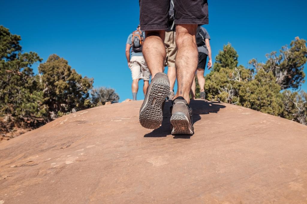 A imagem contém pessoas caminhando por pela superfície de uma rocha.
